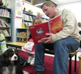 Photo of Albie the dog and a girl and her father reading at the library
