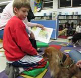 Photo of Aubrey and a boy at the library reading