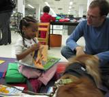 Photo of Aubrey the dog enjoying books at the library