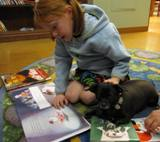 Photo of Ava the dog and a girl and her mom reading