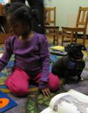 Photo of Ava the dog reading with a girl