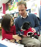 Photo of Ava the dog reading with a girl and her Dad