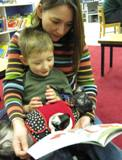 Photo of Ava the dog reading with a boy and his mother