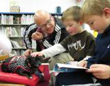 Photo of Ava the dog reading at the library