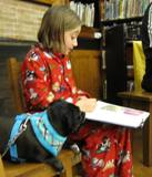 Photo of Ava the dog and a girl reading