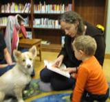 Photo of Bailey the dog listening to a story at the library