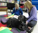 Photo of Buster the dog listening to a girl read