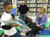 Photo of Buster the dog listening to a boy read