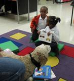 Photo of champ the dog reading with a brother and sister