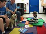 Photo of Champ the dog listening to a boy read