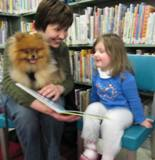 Photo of Chanc the dog and a girl reading at the library