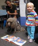 Photo of Ella the dog sharing a story with a little girl