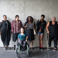 """Six disabled people of color smile and pose in front of a concrete wall. Five people stand in the back, with the Black woman in the center holding up a chalkboard sign reading """"disabled and here."""" A South Asian person in a wheelchair sits in front."""