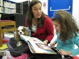 Photo of Fenway the dog reading at the library
