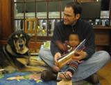 Photo of Freddie the dog reading with a family at the library