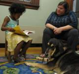 Photo of Freddie the dog listening to a story at the library