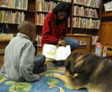 Photo of Freddie and a boy sharing a story at the library