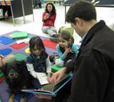 Photo of Happy the dog reading with a family at the library