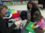 Photo of Happy the dog reading with another family at the library