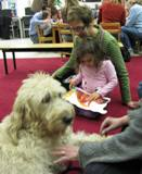 Photo of Harpo the dog reading with a girl and her grandmother