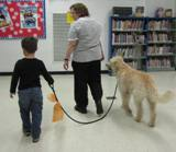 Photo of Harpo the dog going for a stroll with a boy in the library