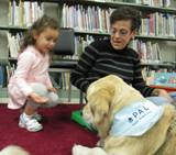 Photo of Leo the dog at the library listening to a story