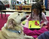 Photo of Leo the dog reading with a little girl