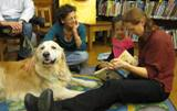 Photo of Leo the dog reading with a family at the library