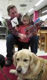Photo of Leo the dog listening to a girl and her father read