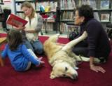 Photo of Leo the dog relaxing at the library listening to a family read a story
