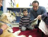 Photo of Leo the dog at the library listening carefully to a boy and his father read a book