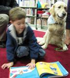 Photo of Leo the dog with a boy reading