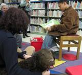 Photo of Max the dog reading with a boy at the library