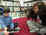 Photo of Max the dog at the library reading with a boy