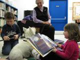 Photo of Nessie the dog and a family reading