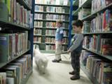 Photo of Nessie the dog walking through the stacks