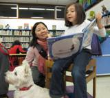 Photo of Nessie the dog reading with a family at the library