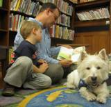 Photo of Pablo the dog hearing a story at the library