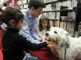 Photo of Pablo the dog and a family smiling at the library