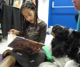 Photo of Pup-a-Roo the dog reading at the library with a girl