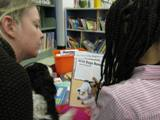 Photo of Pup-a-Roo the dog reading at the library