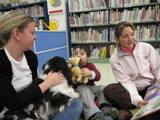 Photo of Pup-a-Roo the dog reading with a family at the library