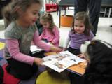 Photo of Pup-a-Roo the dog sharing books with some girls