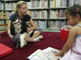 Photo of Pup-a-Roo the dog reading in the library