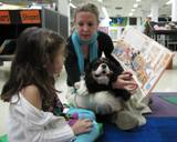 Photo of Pup-a-Roo the dog listening to a story at the library