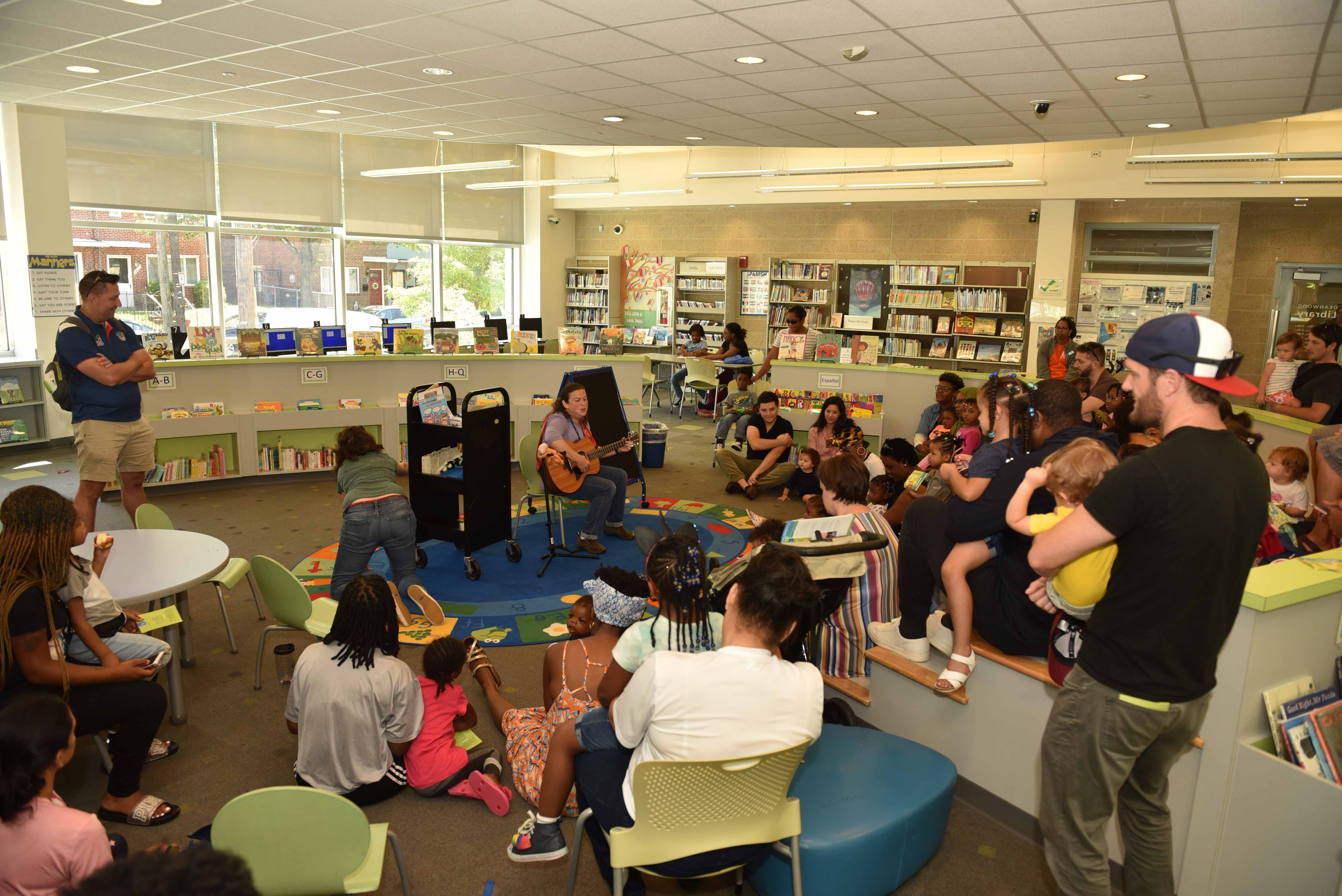 Families participate in story time at Deanwood Library