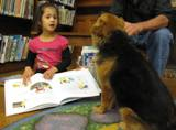 Photo of Trudy the dog reading with a girl at the library