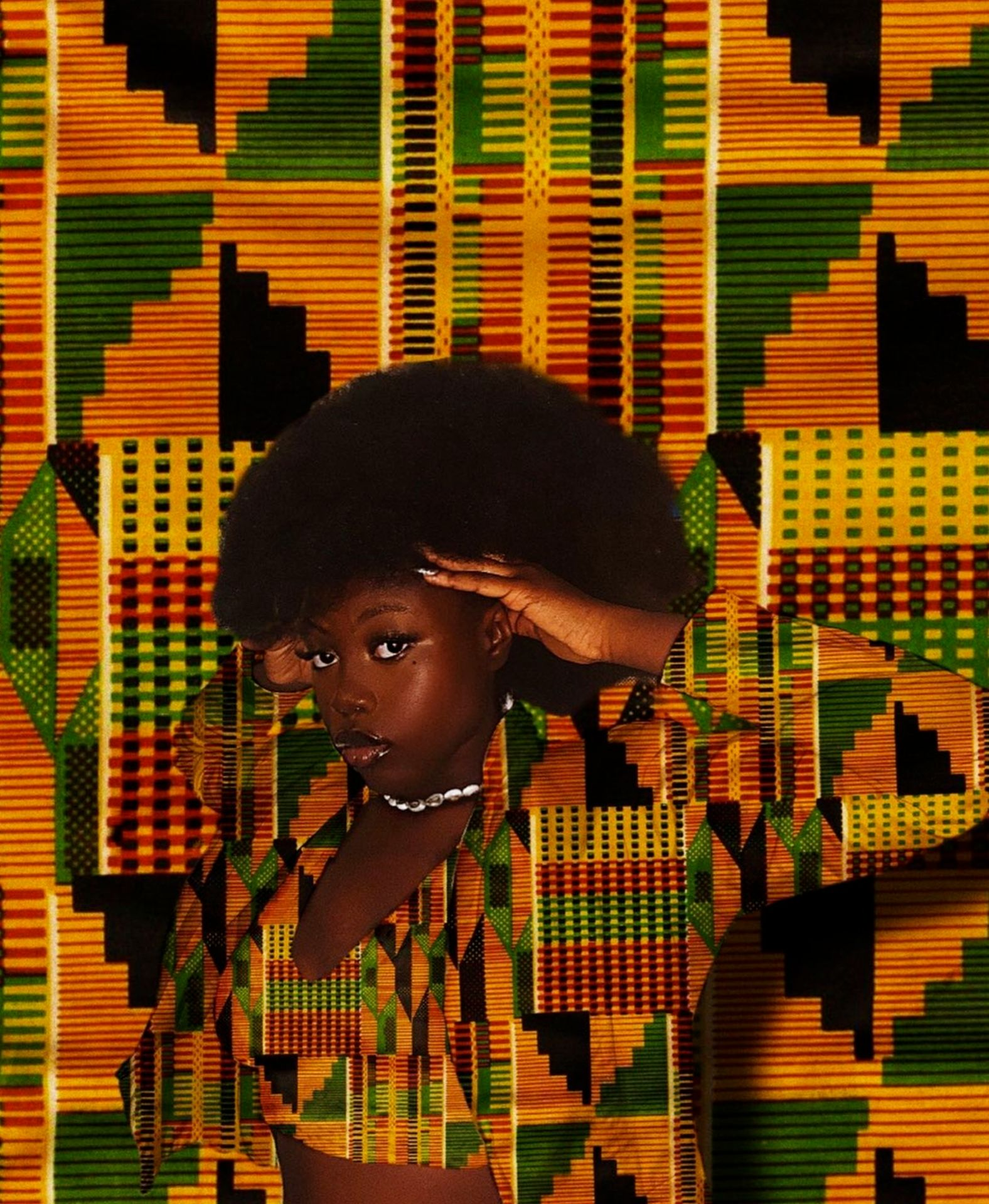A photograph of a black woman posing in colorful kente cloth in front of a kente cloth background