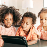Three toddlers watching a show on an ipad