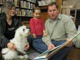 Photo of Willie the dog and a family reading at the library